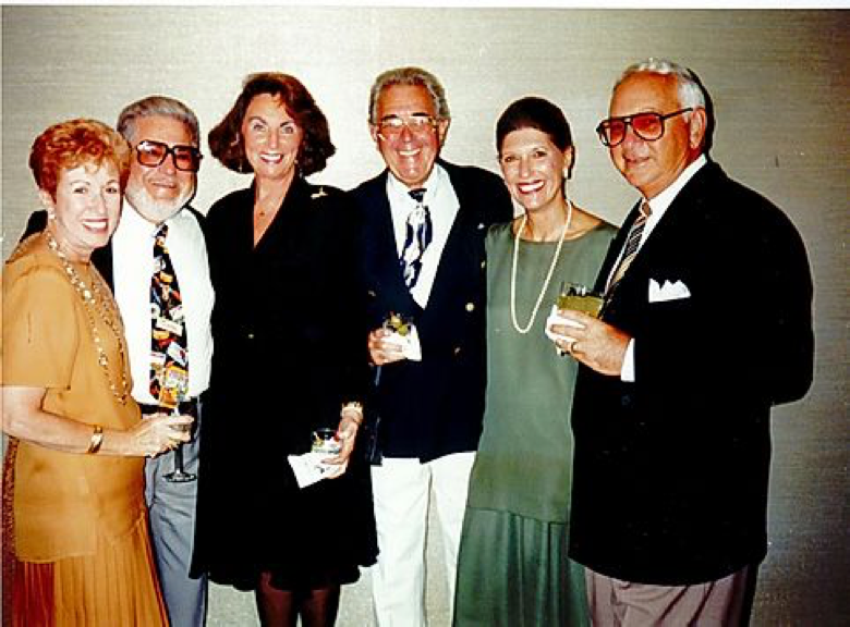 older image eighties style of six adults standing together dressed up holding various martinis