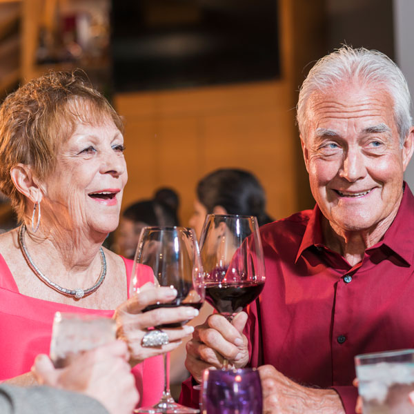 female and male senior clinking wine glasses at dinner table with other older adults and adults in background of resturant