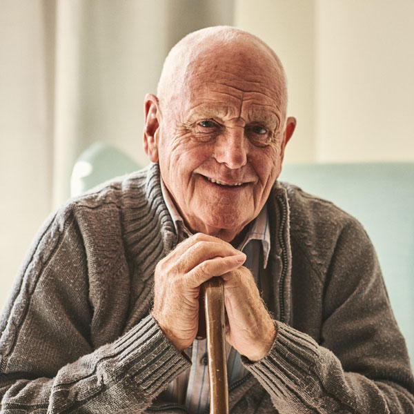 senior male leaning on wooden cane smiling wearing grey sweater over striped buttonup
