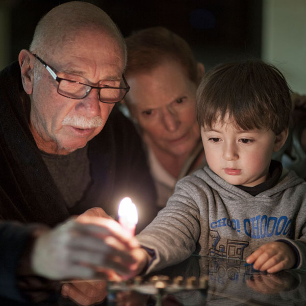 toddler grandson watching grandfather light candle menorah with grandmother watching in background
