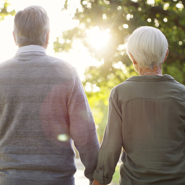 two seniors walking outside with sun peaking through trees holding hands