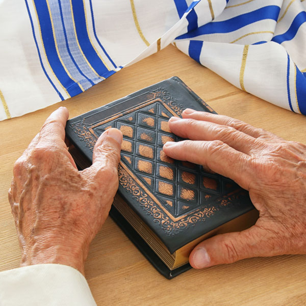 older religious person holding torah with blue white gold linen
