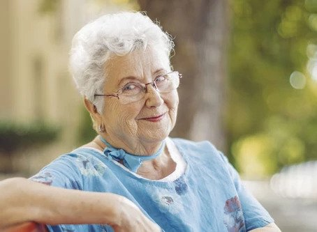 senior female sitting with arm lifted resting on park bench smiling wearing blue shirt and blue bowtie around neck