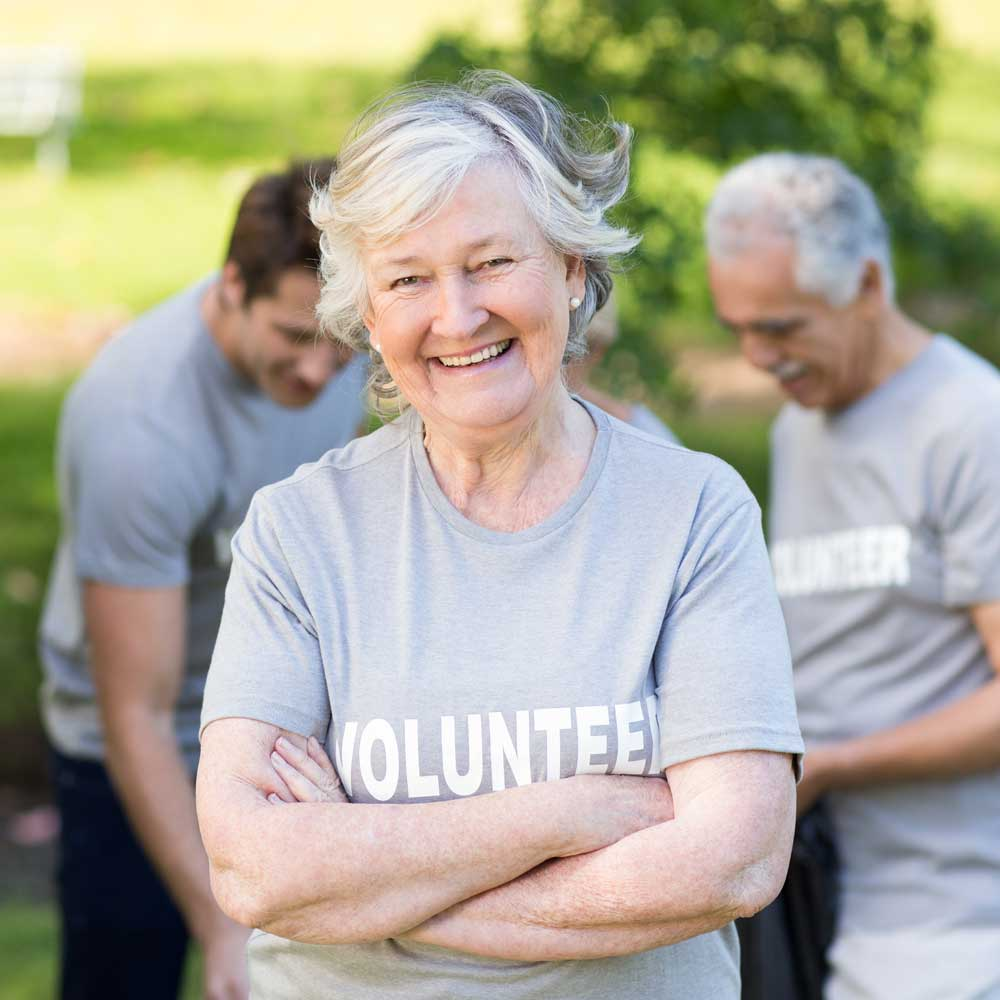 older woman in foreground smiling with arms crossed grey shirt white letters word volunteer two adult men in background