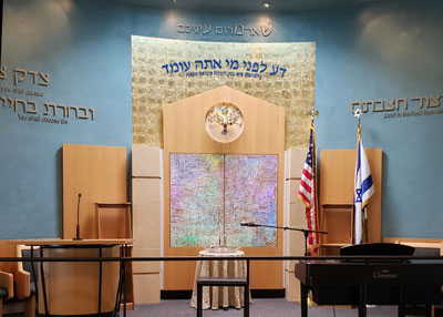 hebrew written on blue walls within room with wood accents railing and piano