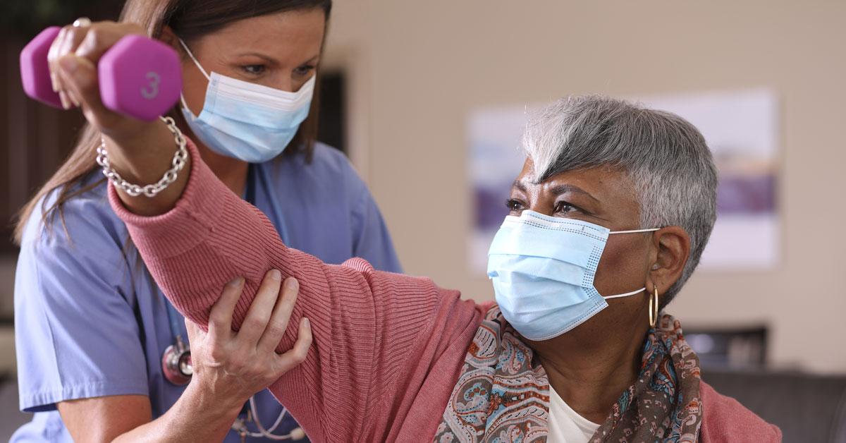 senior female holding weight with support from younger adult female nurse in blue scrubs assiting her both wearing blue paper masks